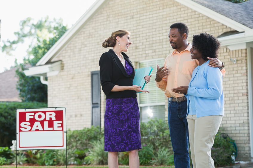 A real estate agent standing in front of a house with a FOR SALE sign in the yard, talking with an African American couple who could be the homeowers, or potential buyers. The agent is wearing a black jacket and purple dress, carrying a blue binder.